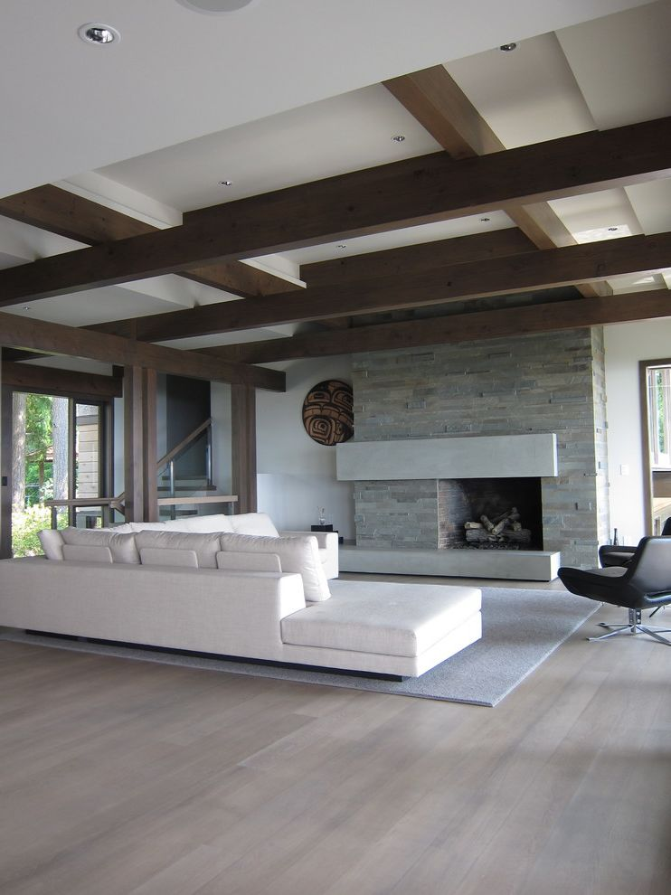 White Wash Wood Floors   Contemporary Living Room  and Concrete Concrete Mantel Fireplace Grey Rug Leather Chair Rug Section Sofa Stained Wood Floor Stone Fireplace White Ceiling White Ceiling and Wood Beams White Section Sofa Wood Beams Wood Floor