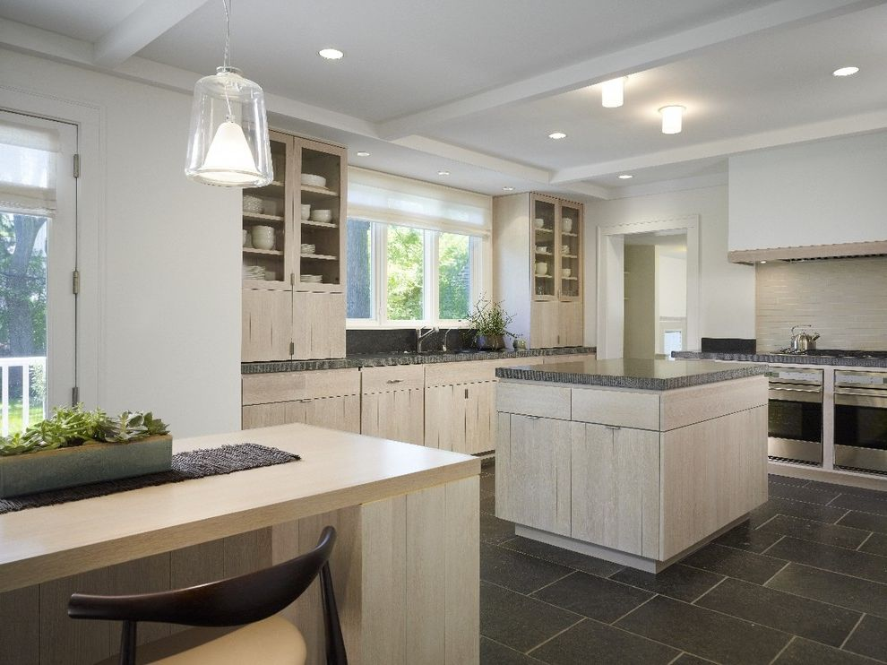 White Wash Wood Floors   Modern Kitchen  and Counter Stools Glass Front Cabinets Hood Kitchen Island Natural Wood Neutral Colors Pendant Lights Recessed Lights Roman Shade Stainless Steel Appliances Tile Floor White