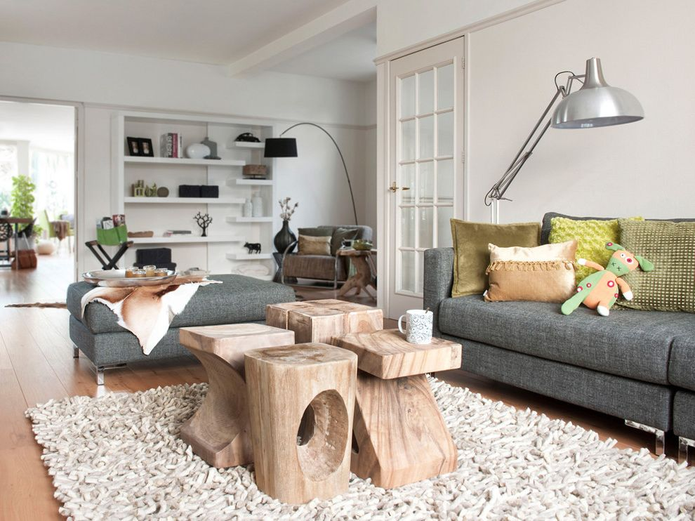 White Washed Wood Coffee Table with Contemporary Living Room  and Arc Lamp Area Rug Bookcase Bookshelves Coffee Table Decorative Pillows Floor Lamp Neutral Colors Stump Table Clustered Tables Swing Arm Lamp Throw Pillows
