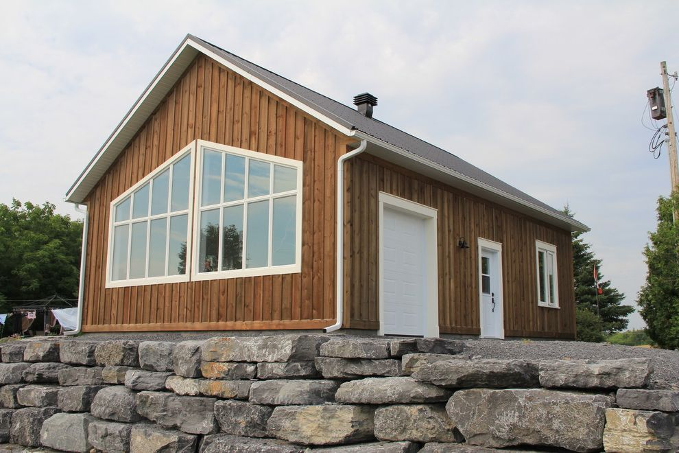 Whites Lumber with Transitional Shed Also Barn Board and Batten Country Gable Roof Garage Gravel Large Windows Rustic Stacked Stone Weathered Siding White Casing White Trim Wood Cladding Wood Siding