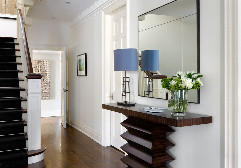 Whitewashed Console Table with Transitional Entry Also Baseboard Black Stair Runner Blue Lampshade Console Table Crown Molding Dark Wood Banister Dark Wood Floor Entry Table Glass Vase Large Vase Mirror Table Lamp White Balustrade White Flowers
