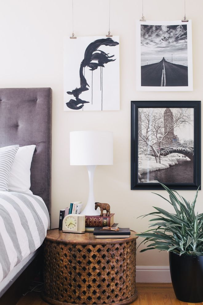 Wire Picture Hanging System   Eclectic Bedroom  and Binder Clip Photo Hangers Black and White Art Carved Wood Side Table Purple Upholstered Headboard Striped Bedding Tufted Hadboard Unframed Artwork White Table Lamp
