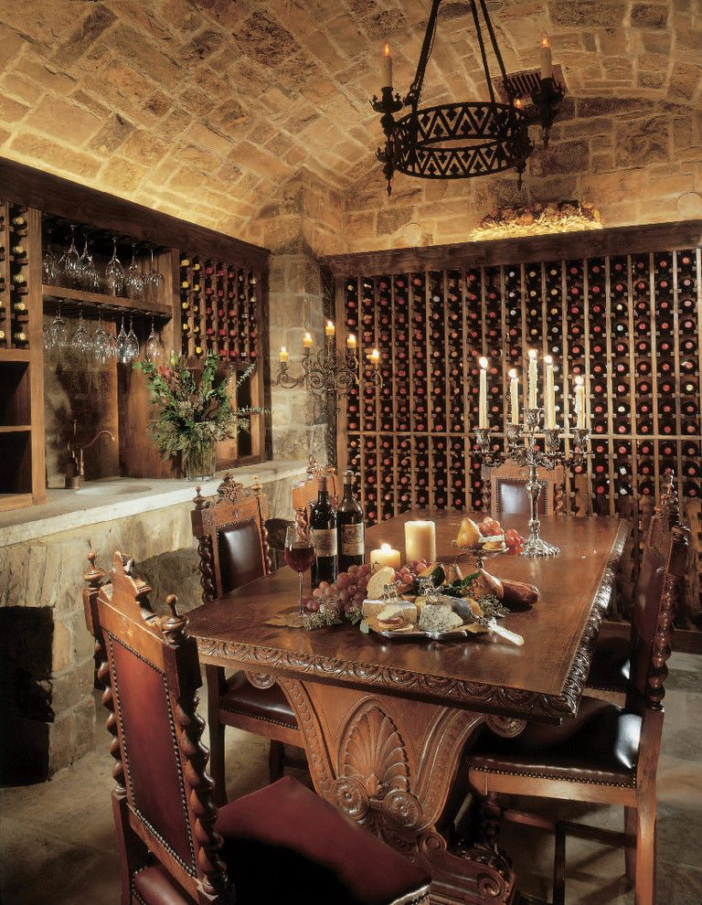 Woodland Park Lodges   Rustic Wine Cellar  and Barrel Vault Built in Storage Candelabra Carved Wood Cave Stone Ceiling Stone Floor Tasting Room Vaulted Ceiling Wine Racks Wine Storage Wineglass Storage Wood Dining Table Woodwork Wrought Iron Chandelier