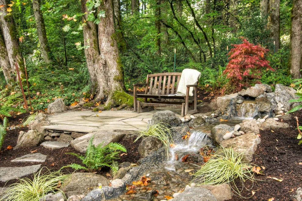 Woodland Park Lodges with Rustic Landscape  and Boulders Creek Ferns Glider Chair Park Bench Patio Furniture Pavers Rocks Rustic Steps Stone Paving Stream Water Feature Wood Bench