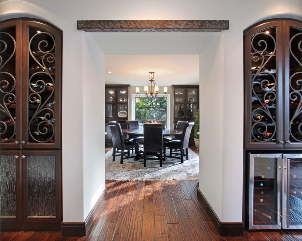 Wrought Iron Storm Doors with Mediterranean Dining Room and Arch Area Rug Beverage Cooler Built in Cabinets Chandelier Dark Stained Wood Glass Front Cabinets Iron Scrollwork Lintel Round Dining Table Specialty Glass White Walls Wine Storage Wood Floor