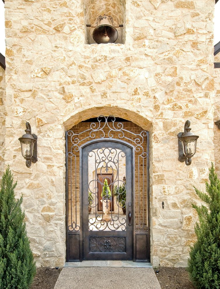 Wrought Iron Storm Doors with Traditional Exterior and Aggregate Concrete Path Arched Doorway Bell Bell Tower Brick Courtyard Iron Work Lantern Wall Sconce Niche Scrollwork Stone Facade