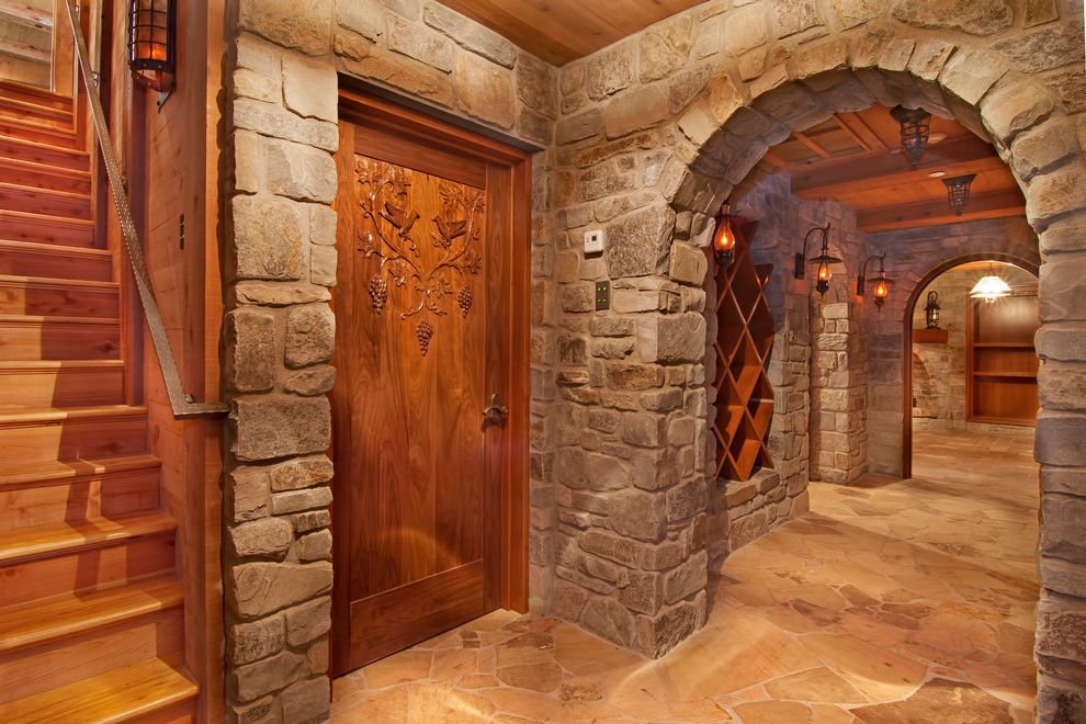 Wyckoff Lighting with Traditional Wine Cellar and Basement Carved Wood Cellar Flagstone Floor Grapes Lanterns Stone Arches Stonework Wine Storage Wood Ceiling Wood Paneling Wrought Iron Handrail