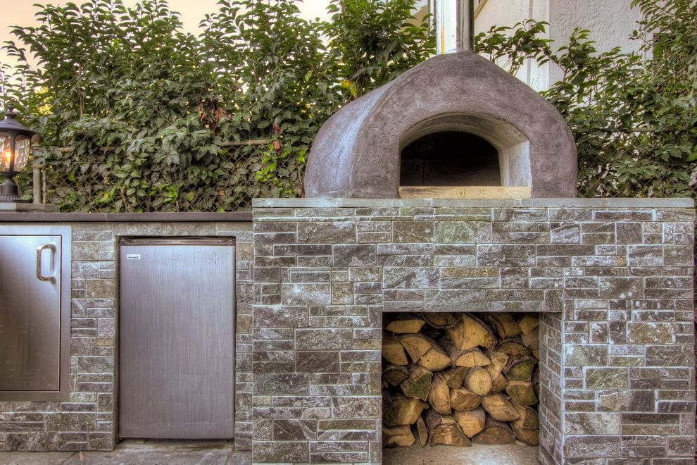 Yellow Brick Pizza with Traditional Patio Also Firewood Storage Mini Refrigerator Neutral Colors Outdoor Kitchen Pizza Oven Stacked Stone Stainless Steel Appliances