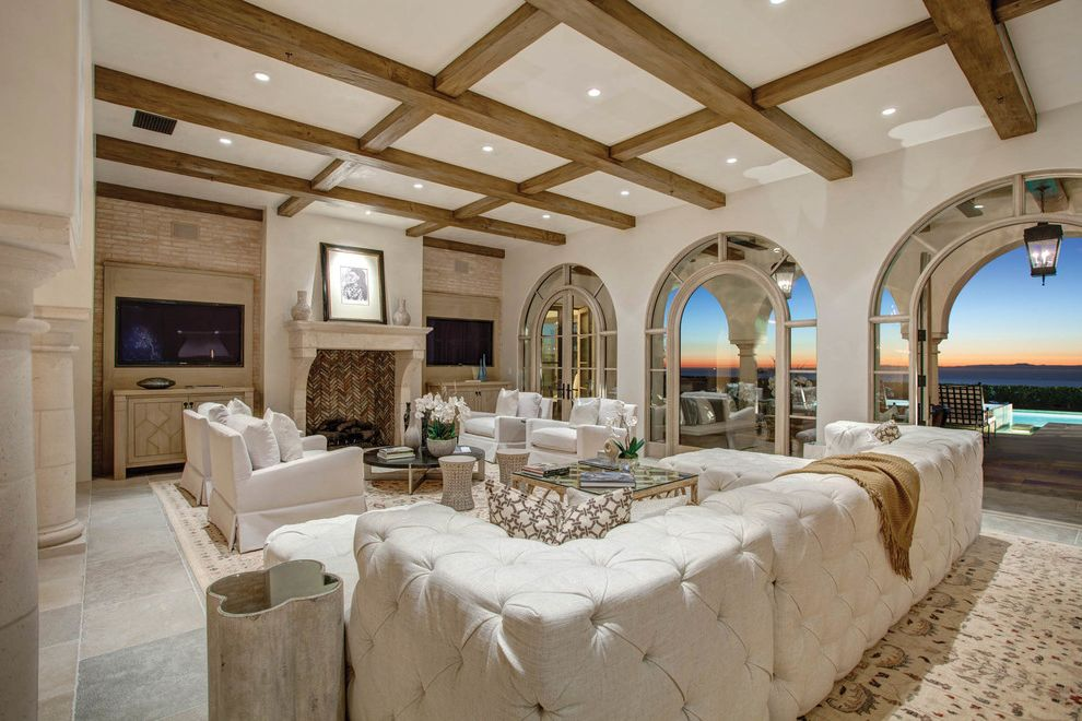 Baers Furniture Orlando   Mediterranean Living Room  and Arched Doorway Arched Window Beamed Ceiling French Doors Glass Doors Gray Floor Tile Tufted Sofa White Armchairs Wood Ceiling Beams