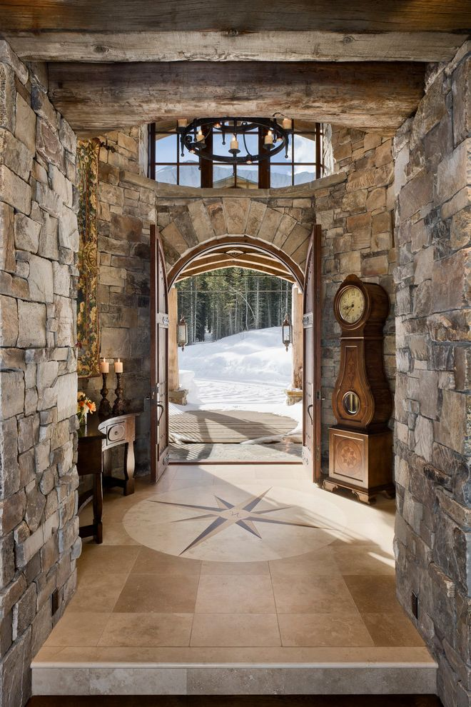 Beauty and the Beast Grandfather Clock   Rustic Entry  and Compass Needle Curved Console Entry Grandfather Clock Interior Round Chandelier Rustic Wood Rustic Wood Beams Stone Stone Voussoirs Stone Walls Tile Floor