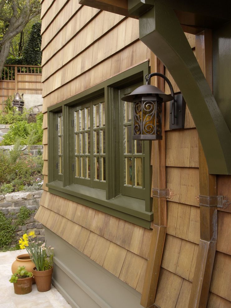 Bob Green Siding with Rustic Spaces Also Casement Windows Green Trim Hillside House Plants Lanterns Neutral Colors Outdoor Lighting Potted Plants Rain Gutters Retaining Walls Rustic Shingle Siding Slope Terrace