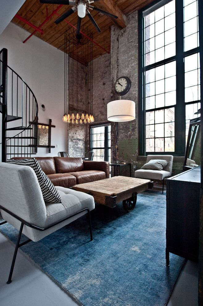 Cotton Mill Lofts with Industrial Living Room  and Apartment Living Black and White Throw Pillow Black Ceiling Fan Gray Chair Hanging Lightbulbs Industrial Loft Leather Couch Loft Style Rustic Coffee Table Spiral Staircase
