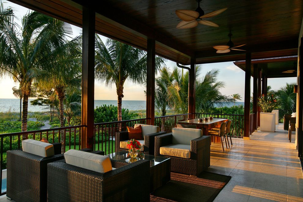 Dream World Furniture with Tropical Porch  and Ceiling Fan Coast Neutral Colors Ocean Outdoor Cushion Outdoor Dining Outdoor Entertaining Overhang Palm Tree Rattan Furniture Tile Flooring View Waterfront Wood Ceiling Wood Post