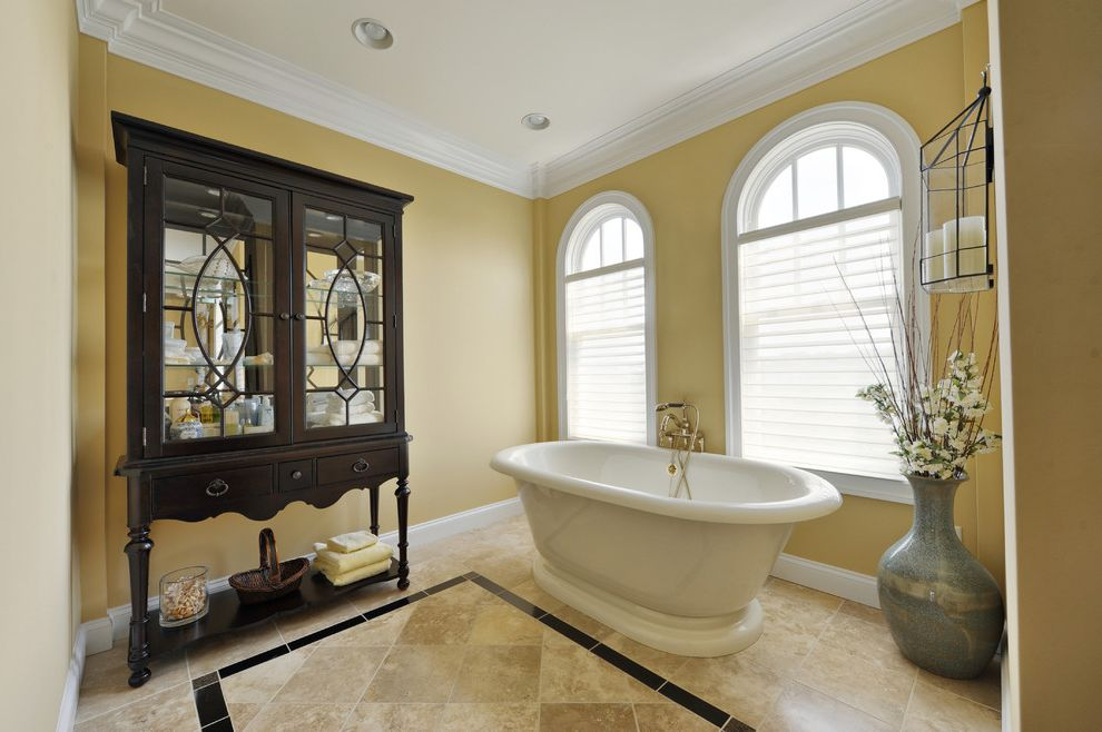 Echelon Furniture with Traditional Bathroom  and Arched Windows Crown Molding Dark Stained Wood Free Standing Tub Glass Front Cabinet Hutch Radius Windows Sheer Blinds Travertine Vase White Trim Yellow