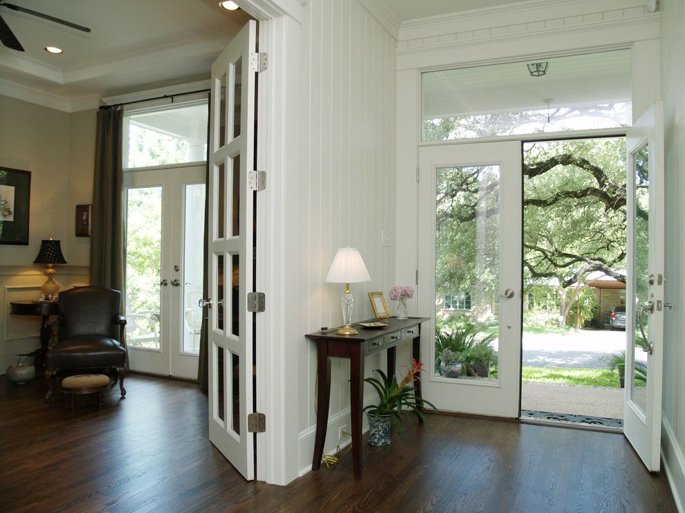 Entry Way Tables   Traditional Entry Also Ceiling Fan Console Table Dark Stained Wood Floor French Doors Glass Doors Leather Arm Chair Tongue and Groove Paneling Transom Window Wainscot White Trim White Walls