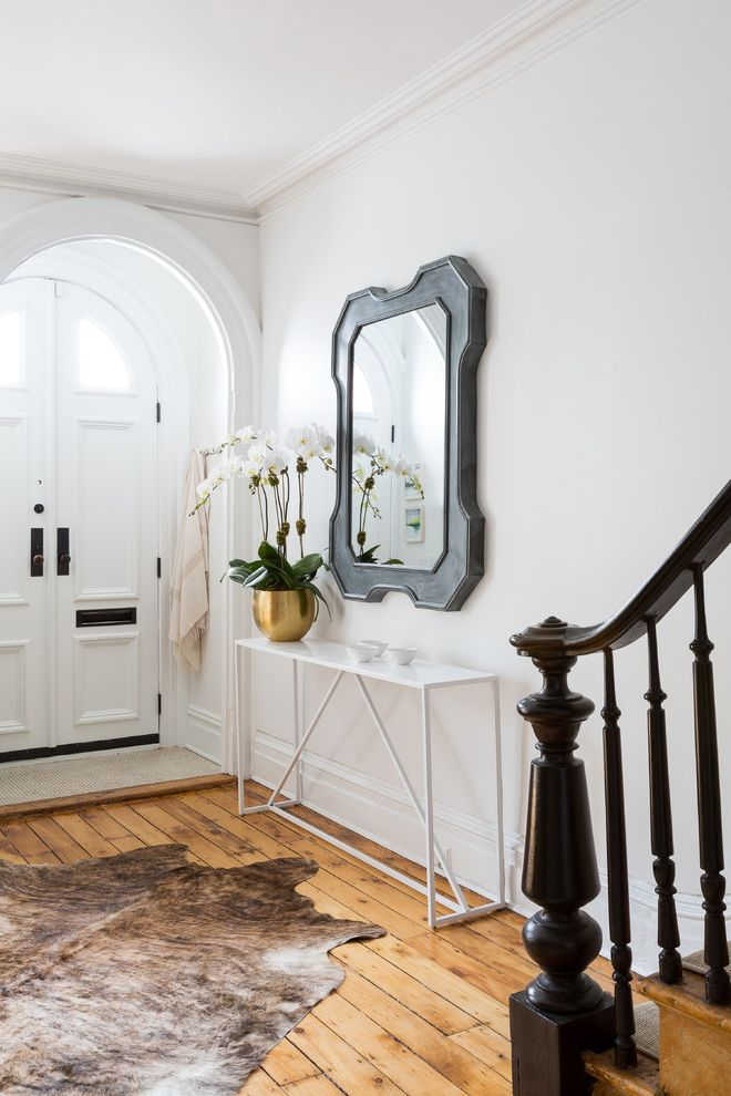 Entry Way Tables   Transitional Entry Also Animal Skin Rug Arched Door Banister Black Metal Console Table Cowhide Metal Mirror Newel Post Orchids White Door White Table