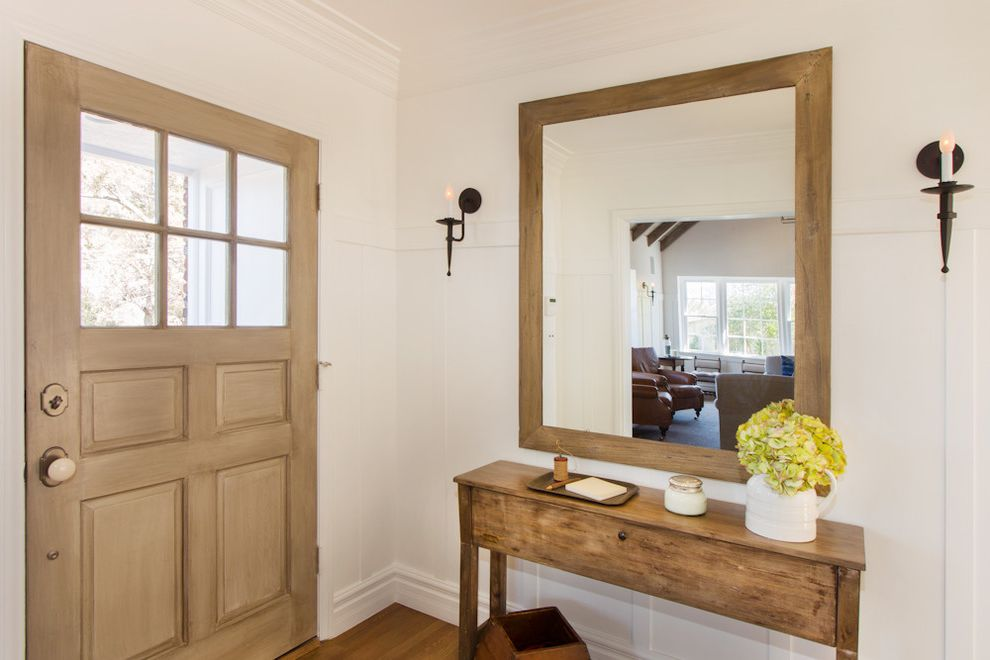 Entry Way Tables with Traditional Entry Also Baseboard Candle Sconce Crown Molding Foyer Front Door Light Wood Muntins Neutral Colors Paneled Door Paneling Potted Plant Wall Mirror White Trim White Walls Wood Console