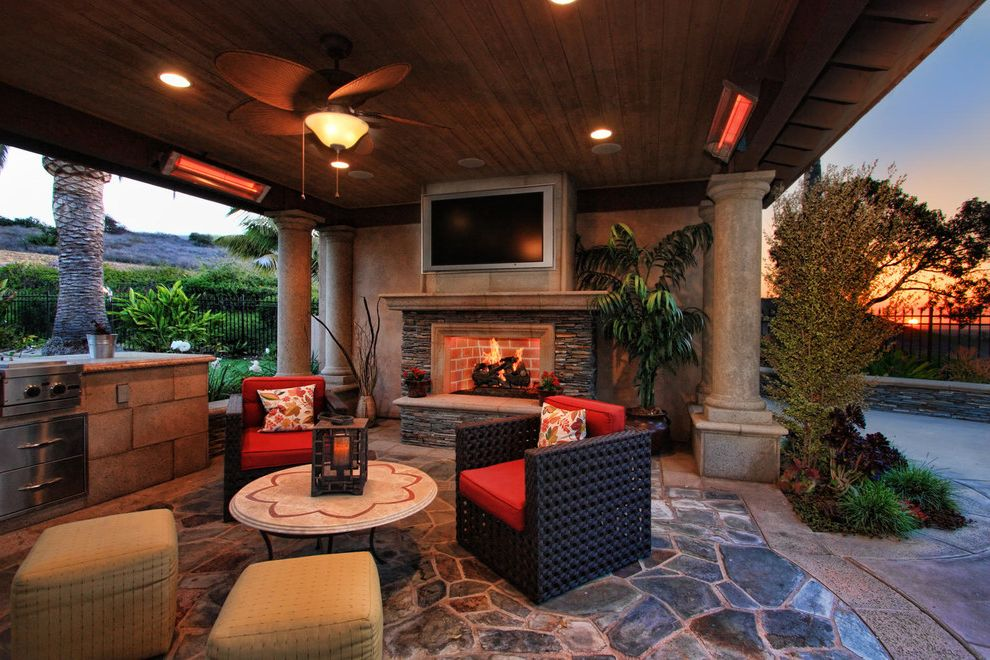 Fake Fireplace Heater with Traditional Patio  and Ceiling Fan Outdoor Entertaining Outdoor Grill Outdoor Heating Outdoor Living Outdoor Living Room Palm Tree Pilars Ramada Recessed Lighting Red Cushions Staging Stone Floor Wood Panel Ceiling