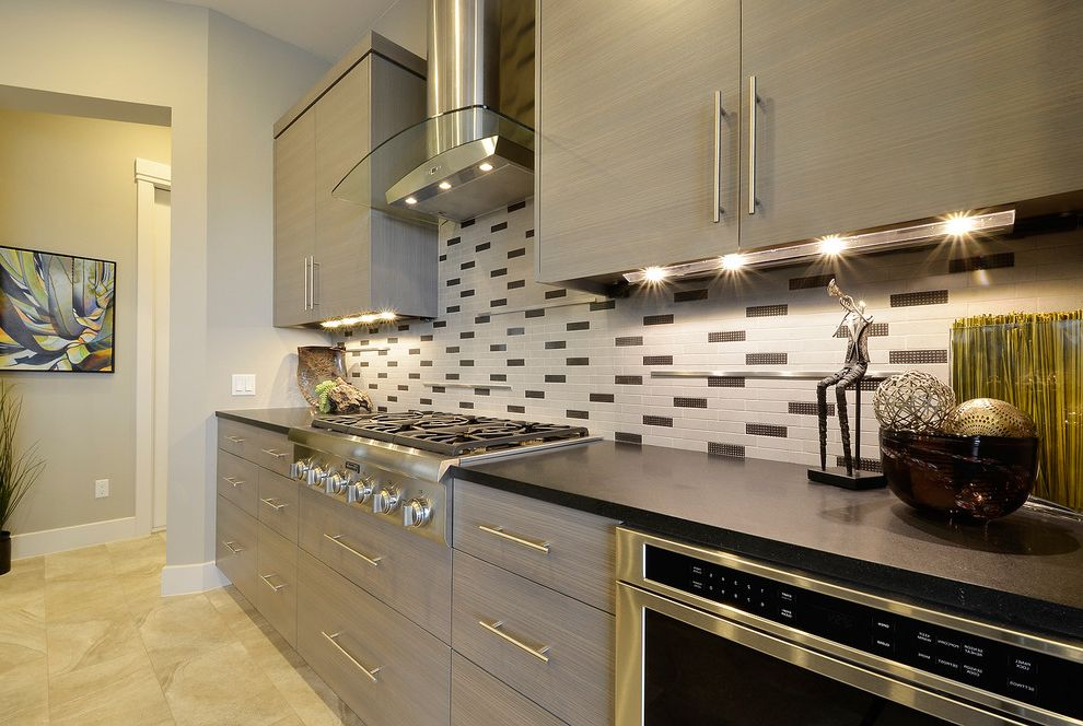 Houston Custom Installers with Contemporary Kitchen  and Beige Tile Floor Black Tile Backsplash Cooktop Gray Cabinets Gray Drawers Gray Tile Backsplash Gray Wall Range Hood Stainless Steel Under Cabinet Lighting White Molding