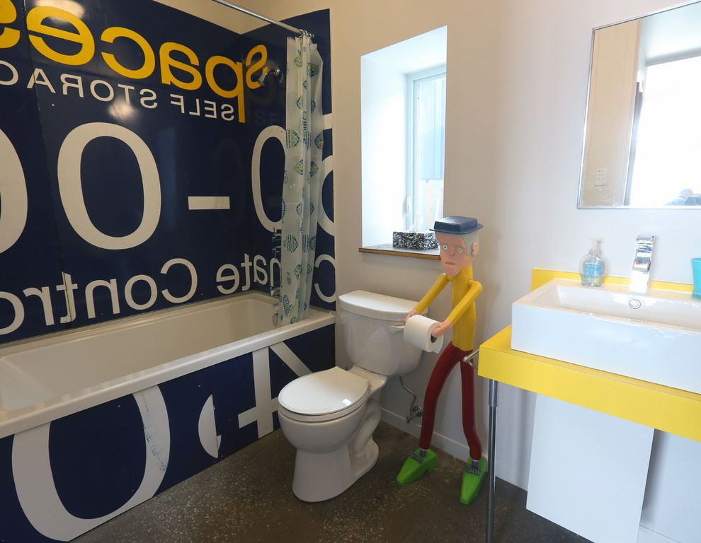 Install Toilet Paper Holder   Eclectic Bathroom  and Bathtub Comical Concrete Floor Playful Salvaged Sign Shower Curtain Shower Over Bathtub Toilet Paper Holder Vessel Sink Vintage Sign White Walls Window Ledge Yellow Vanity
