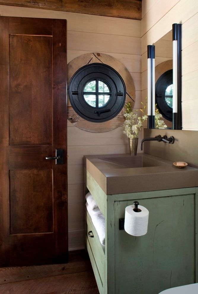 Install Toilet Paper Holder   Rustic Powder Room  and Concrete Countertop Concrete Sink Dark Hardware Green Vanity Mirror Porthole Window Round Window Sconce Towel Storage Wood Door Wood Paneling