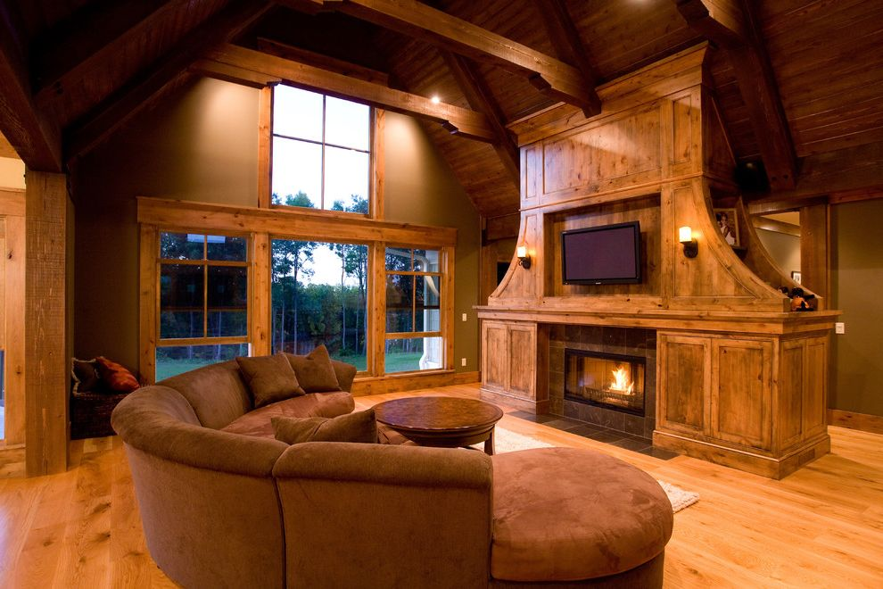 Kidney Shaped Couch with Farmhouse Family Room Also Barn Beams Fireplace High Ceiling Patio Door Round Sofa Tv Above Fireplace Vaulted Ceiling Windows Wood Beams Wood Cabinets Around Fireplace Wood Ceiling Wood Floor Wood Trim