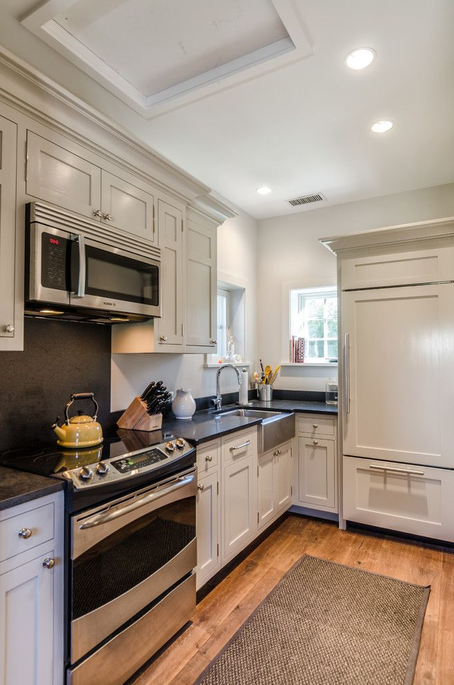 Microwave Above Stove   Rustic Kitchen  and Beige Cabinets Beige Drawers Black Backsplash Black Stove Backsplash Farmhouse Sink Galley Kitchen Hidden Refrigerator Panel Refrigerator Recessed Lighting Rustic Wood Floor Stainless Steel Sink Window Ledge