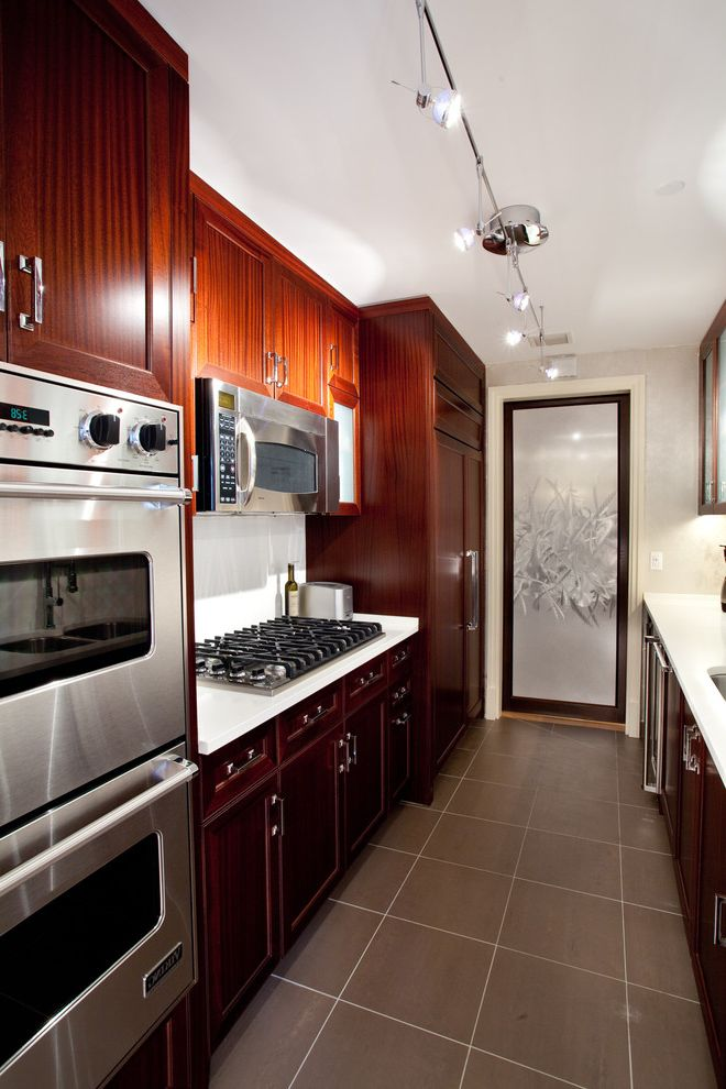 Microwave Above Stove with Traditional Kitchen  and Bachelor Pad Built in Range Cherry Wood Cabinets Galley Kitchen Masculine Kitchen Modern Kitchen Shaker Style Spotlighting Stainless Steel Appliances White Walls