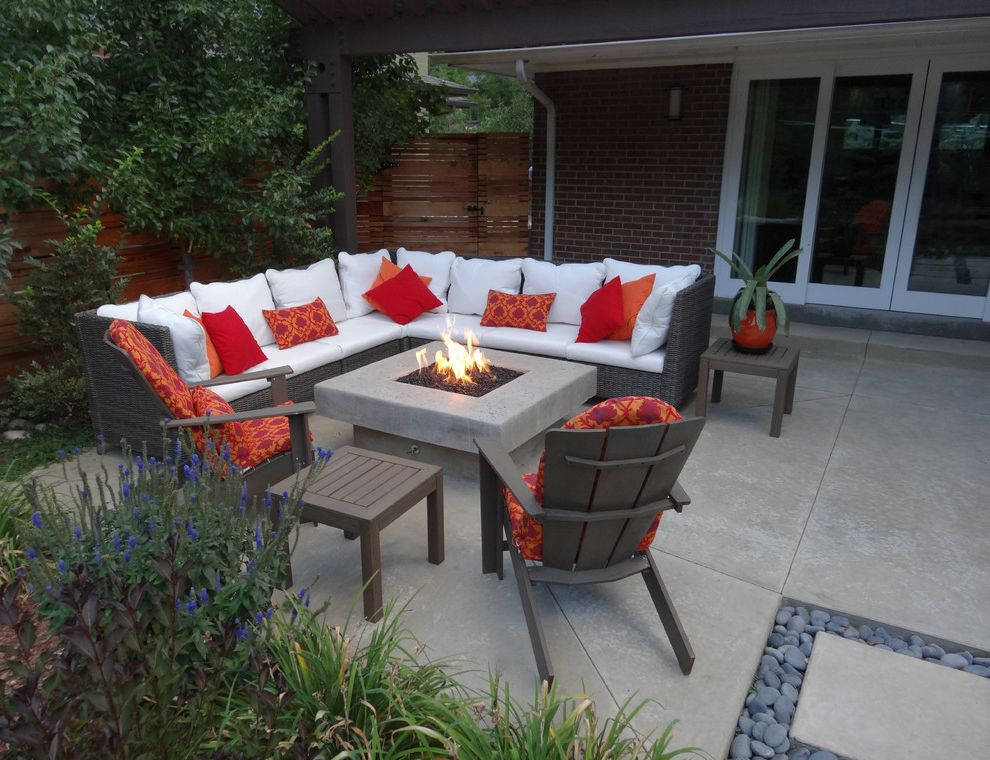 Mile High Ministries   Contemporary Patio  and Black Smooth Stones Brick Exteriors Concrete Patio Contemporary Back Yard Cool Outdoor Living Space Modern Fire Pit Outdoor Entertaining Outdoor Furniture Red Accents Wood Fence