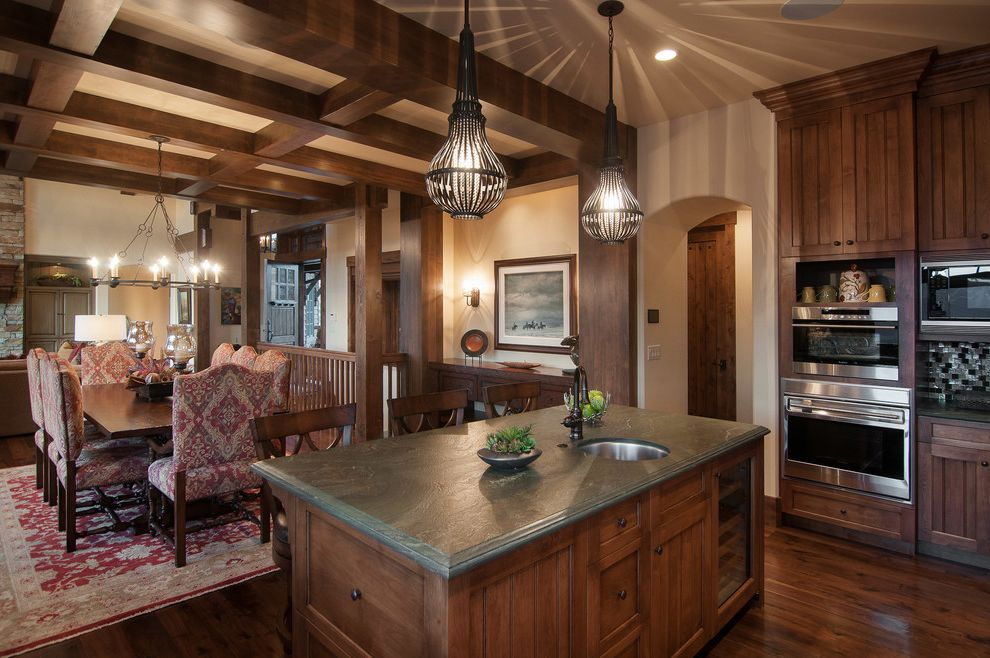 Park City Showcase of Homes   Rustic Kitchen  and Arch Coffered Ceiling Exposed Beams Fully Upholstered Dining Chairs Green Countertop Island Pendants Prep Sink Red Persian Rug Shadows