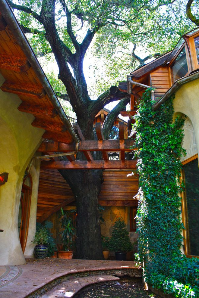 Rainbow Tree Care   Eclectic Landscape  and Arched Doorway Bay Window Covered Patio Eaves Flagstone Patio Ivy Landscaping Lawn Outdoor Fireplace Pergola Steps Stucco Wood Trim Woven Outdoor Furniture
