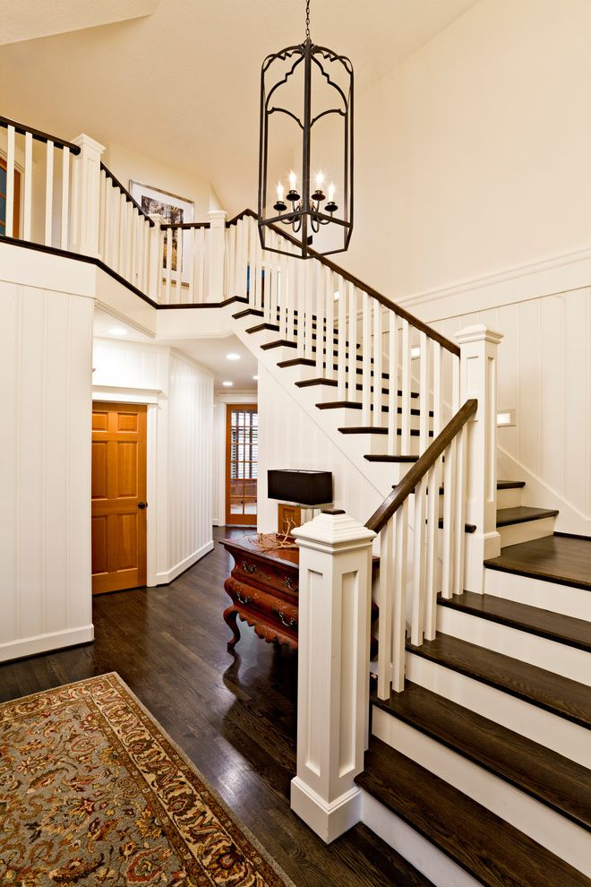 Replacing Carpet on Stairs with Traditional Staircase Also Area Rug Console Dark Wood Floors Dark Wood Tread Entry Foyer Hall Landing Pendant Lighting White Banister White Paneling White Risers White Wall Wood Door Wood Handrail