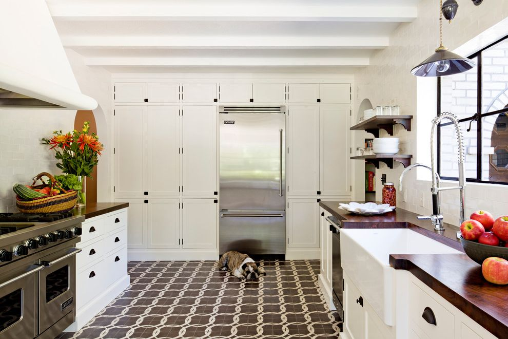 Ruvati Sinks with Mediterranean Kitchen  and Apron Front Sink Bin Pull Cabinets Encaustic Tile Farmhouse Sink Floating Shelves Flowers Market Basket Pendant Light Spanish Revival Tile Backsplash Walnut Counter
