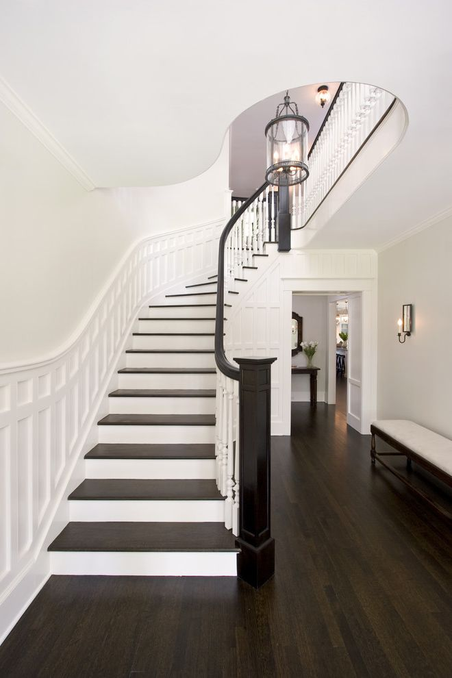 Sanding and Staining Wood Floors with Traditional Staircase  and Banister Curved Staircase Dark Floor Entrance Entry Entry Lantern Foyer Wainscoting White Wood Winders Wood Flooring Wood Molding Wood Railing Wooden Staircase