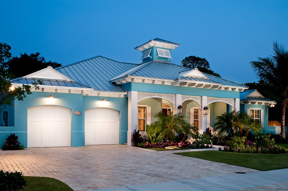 The Porch Key West   Tropical Exterior  and Arched Garage Doors Blue House Brick Driveway Front Yard Landscaping Garage Lighting Outdoor Lighting Plants and Flowers Tropical Landscaping Vertical Metal Roof Wall Lanterns