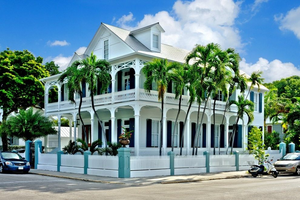 The Porch Key West with Tropical Exterior  and Corner Lot Covered Bacony Dormer Double Porch Light Blue Ornate Railing Palm Trees Picket Fence Victorian Wraparound Balcony Wraparound Porch
