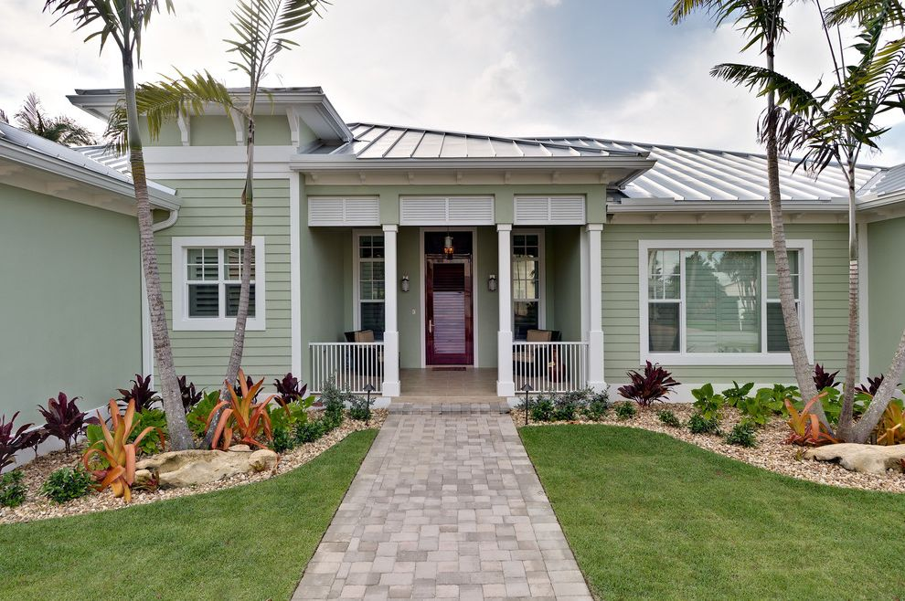 The Porch Key West with Tropical Exterior  and Covered Porch Landscaping Palm Tress Pathway Standing Seam Metal Roof Walkway White Posts White Railing White Trim