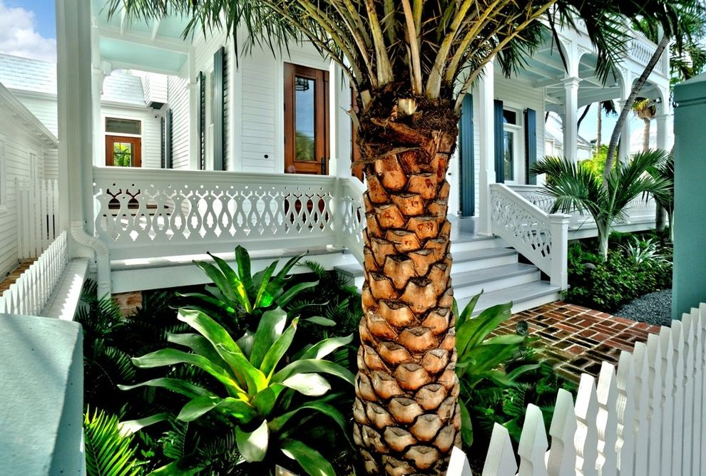 The Porch Key West with Tropical Porch  and Brick Path Columns Covered Porch Fretwork Lap Siding Light Blue Ornate Railing Palm Trees Picket Fence Shutters Steps Victorian Wood Entry Door Wraparound Porch