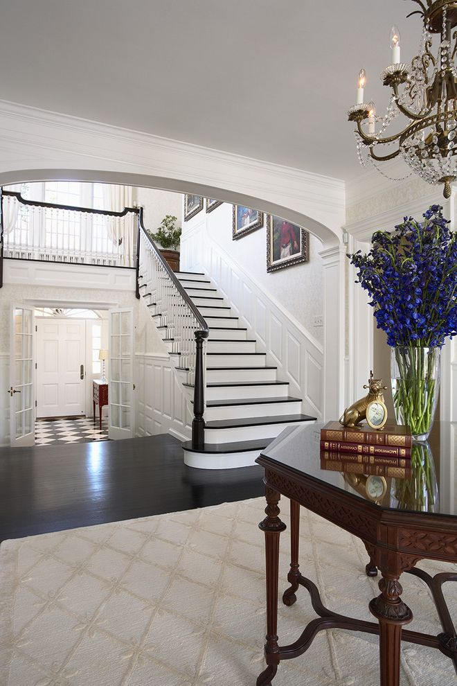What is Kilz Used for   Traditional Entry  and Area Rug Banister Black and White Chandelier Dark Floor Entry Table Floral Arrangement Foyer Handrail Harlequin Floor Pattern Wainscoting Wall Art Wall Decor Wood Railing Wooden Staircase