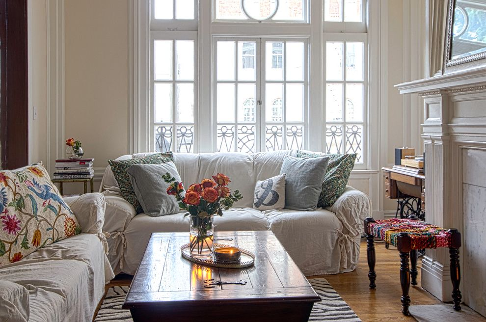 White Slip Covered Sofa   Shabby Chic Style Living Room  and Casement Windows Crewel Work Fireplace Mantel Marble Mirror Muntins Pillows Rustic Coffee Table Tall Ceilings Tall Windows Urban White Painted Molding Zebra Rug