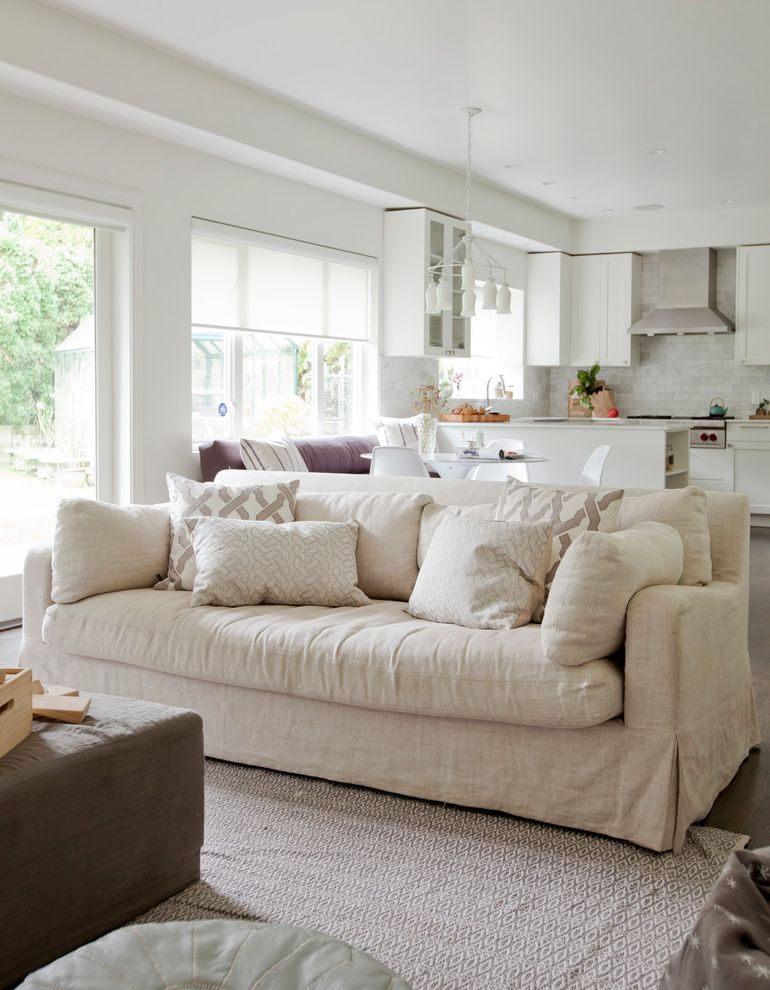 White Slip Covered Sofa   Transitional Family Room  and Beige Sofa Brown Ottoman Chandelier Great Room Neutral Area Rug Neutral Fabrics Patterned Pillows Soffit