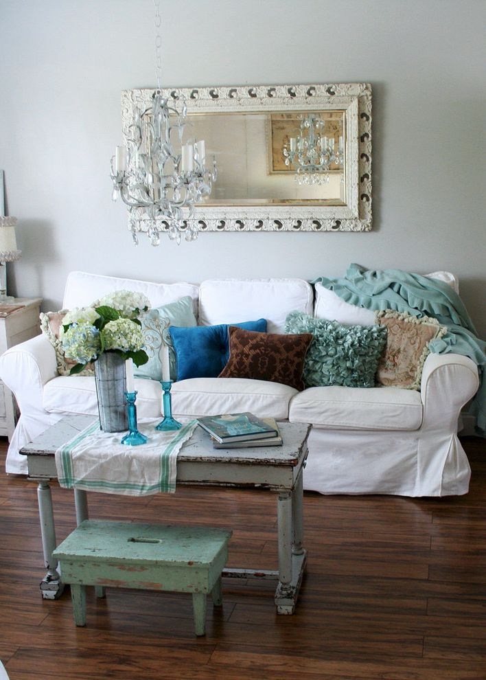 White Slip Covered Sofa with Shabby Chic Style Living Room  and Crystal Chandelier Framed Mirror French Hydrangia Maple Syrup Bucket Mirror Shabby Chic Slipcovers Throw Pillows Vintage White Sofa Wood Table