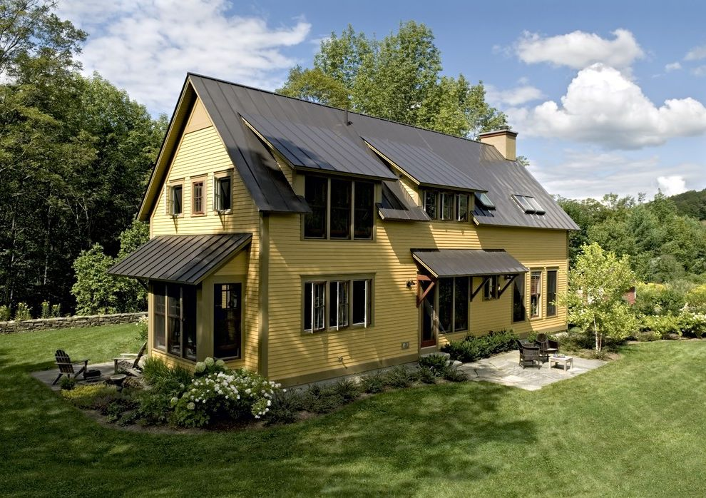 Brad Smith Roofing   Farmhouse Exterior  and Bold Colors Casement Windows Dormer Windows Farmhouse Grass Lawn Metal Roof Patio Patio Furniture Rustic Skylights Standing Seam Roof Turf Wood Siding Wood Trim Yellow House