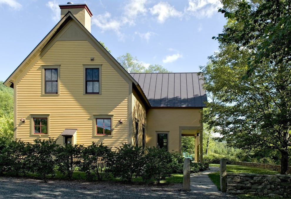 Brad Smith Roofing with Farmhouse Exterior  and Eaves Entrance Entry Farmhouse Gabled Roof Hedge Metal Roof Overhang Path Porch Rock Wall Rustic Stacked Stone Standing Seam Roof Stone Wall Walkway Wood Siding Yellow Walls