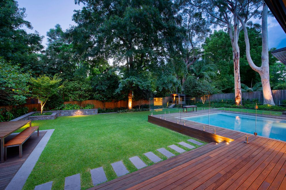 How to Build a Deck Around a Pool with Contemporary Landscape  and Backyard Bench Deck Garden Glass Enclosure Grass Hardscape Landscape Lawn Outdoor Dining Outdoor Lighting Poolside Rectangular Pool Stone Retaining Wall Table