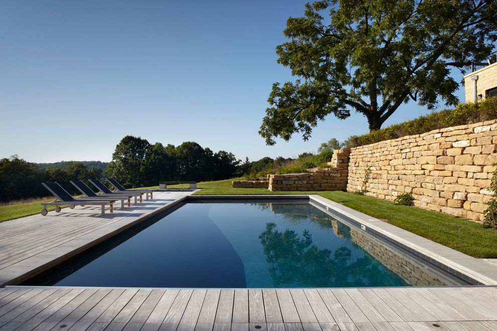 How to Build a Deck Around a Pool with Farmhouse Pool  and Chaise Lounge Deck Farm House Grass Hillside Lawn Minimalist Modern Barn Patio Furniture Shade Tree Slope Stone Retaining Wall Sustainable Terraced Turf View