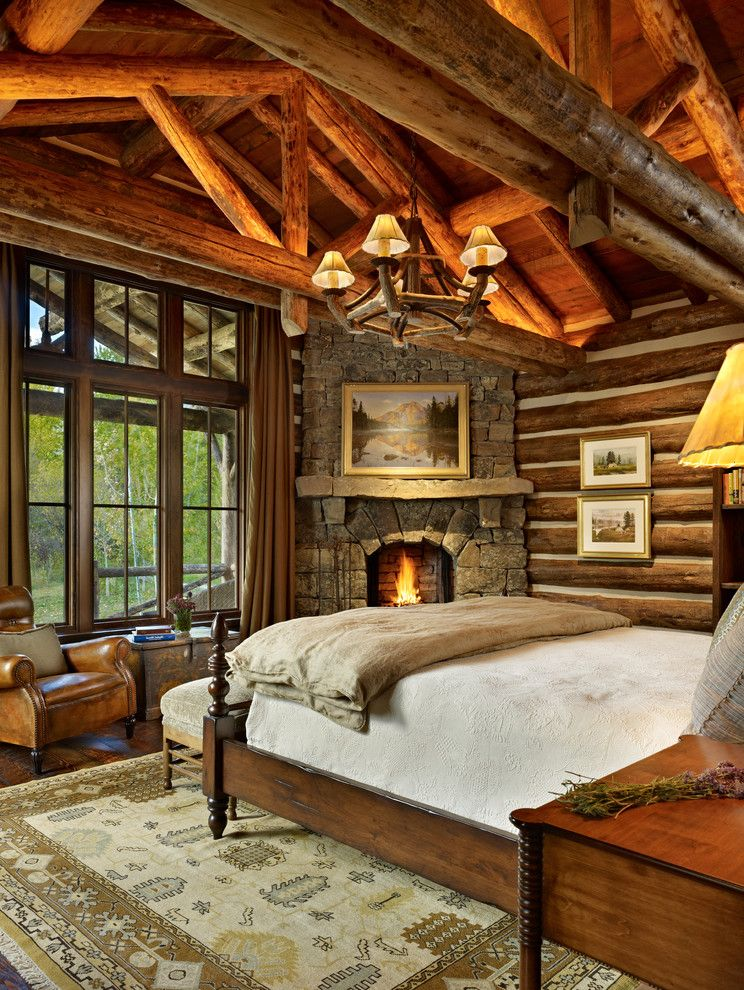 Log Cabin Builders in Texas with Rustic Bedroom Also Cathedral Ceiling Chinking Exposed Beams Fireplace Landscape Painting Leather Arm Chair Log Cabin Raked Ceiling Rough Hewn Wood Stone Chimney Stone Fireplace Truss Wooden Bed