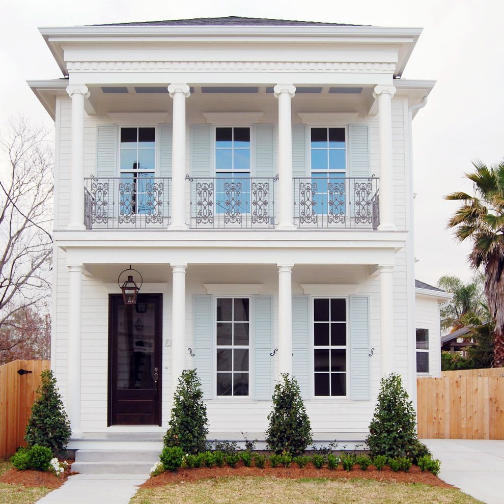 New Orleans Millworks   Traditional Exterior  and Balcony Black Door Dentil Trim Filagree Balcony Railing Ionic Columns Pale Blue Shutters Porch Columns Porch Light Sash Door Topiary Two Story White House White Siding