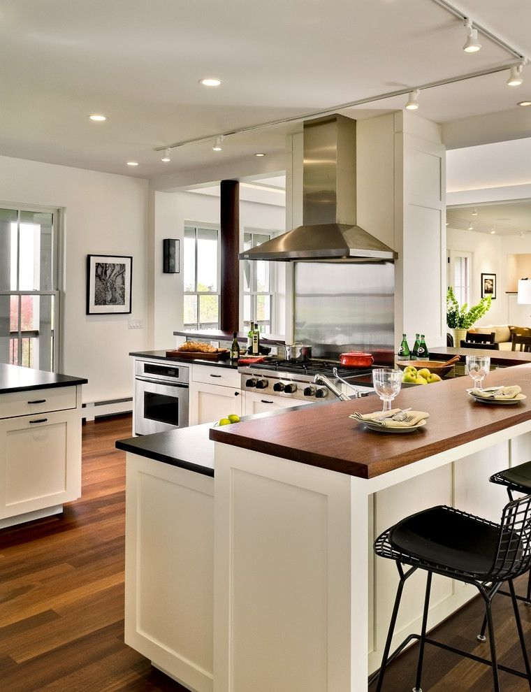 Ada Counter Height with Contemporary Kitchen  and Black Countertops Breakfast Bar Ceiling Lighting Concrete Floor Eat in Kitchen Great Room Kitchen Island Range Hood Shaker Cabinets Stainless Steel Appliances Track Lighting Wood Countertops Wood Floors