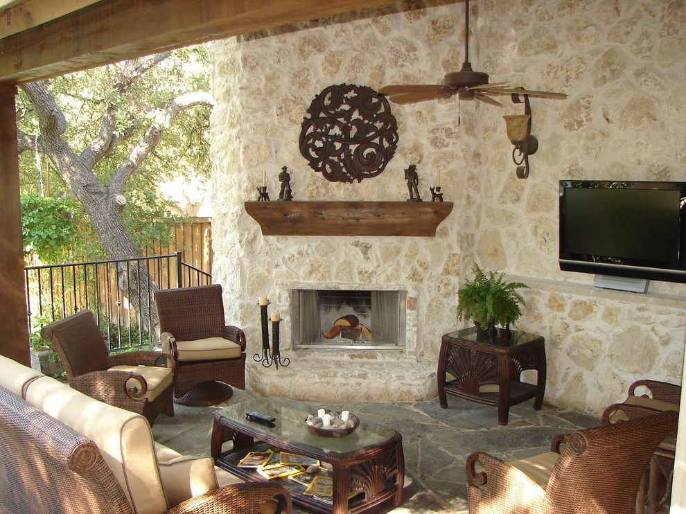 Annies Austin   Traditional Patio Also Ceiling Fan Coffee Table Fireplace Outdoor Tv Patio Side Table Stone Floor Stone Wall Tropical Wall Mounted Outdoor Tv Wicker Chair Wicker Furniture Wood Beams Wood Mantle Wood Shelf